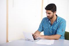 Homem novo que usa um computador Fotos de Stock Royalty Free