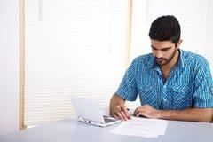 Homem novo que usa um computador Imagens de Stock
