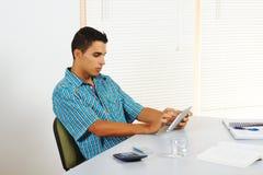 Homem novo que usa um PC da tabuleta Foto de Stock