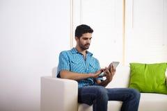 Homem novo que usa um PC da tabuleta Foto de Stock Royalty Free