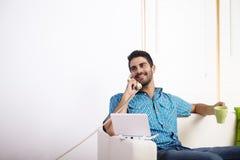 Homem novo que usa um portátil Fotos de Stock Royalty Free