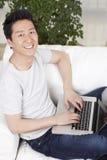 Homem novo que usa um portátil no sofá Foto de Stock