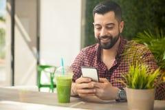 Homem novo que usa um smartphone imagem de stock royalty free