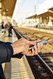 Homem novo que usa um smartphone em um estação de caminhos-de-ferro Imagem de Stock Royalty Free
