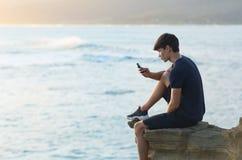 Homem novo que usa um telefone celular na praia durante o por do sol foto de stock