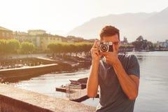 Homem novo que usa uma câmera do vintage na frente do passeio do lago em Ascona fotos de stock