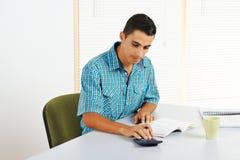 Homem novo que usa uma calculadora Fotografia de Stock