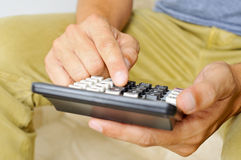 Homem novo que usa uma calculadora Imagens de Stock Royalty Free