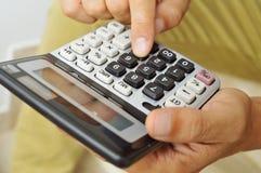 Homem novo que usa uma calculadora Fotografia de Stock Royalty Free