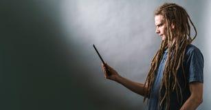 Homem novo que usa uma tabuleta em um fundo escuro fotografia de stock