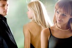 Homem novo que vai com amiga e que olha a mulher nova Fotos de Stock