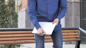 Homem novo que vem e que senta-se no banco usar o portátil video estoque