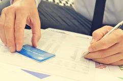 Homem novo que verifica a informação de seu cartão de crédito Imagens de Stock Royalty Free
