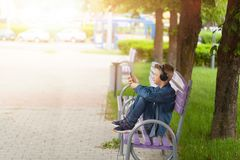 Homem novo que verifica seu telefone celular fora O adolescente nos fones de ouvido usa seu smartphone fotografia de stock royalty free