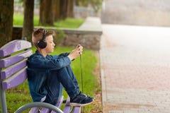 Homem novo que verifica seu telefone celular fora O adolescente nos fones de ouvido usa seu smartphone imagens de stock