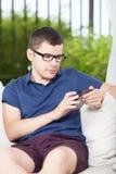 Homem novo que verifica sms Fotografia de Stock Royalty Free