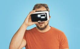 Homem novo que veste óculos de proteção da realidade virtual de VR Fotografia de Stock