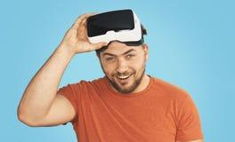 Homem novo que veste óculos de proteção da realidade virtual de VR Imagens de Stock