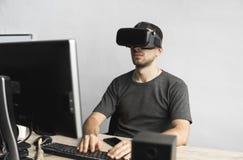 Homem novo que veste auriculares dos óculos de proteção da realidade virtual, caixa do vr e sentando-se no escritório contra o mo foto de stock