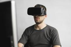 Homem novo que veste auriculares dos óculos de proteção da realidade virtual, caixa do vr e sentando-se no escritório contra o mo imagem de stock royalty free