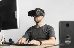 Homem novo que veste auriculares dos óculos de proteção da realidade virtual, caixa do vr e sentando-se no escritório contra o mo fotos de stock royalty free