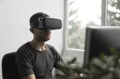 Homem novo que veste auriculares dos óculos de proteção da realidade virtual, caixa do vr e sentando-se no escritório contra o mo fotografia de stock royalty free