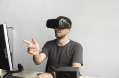 Homem novo que veste auriculares dos óculos de proteção da realidade virtual e que senta-se no escritório contra o computador Con fotos de stock