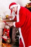 Homem novo que veste como Papai Noel. Fotos de Stock