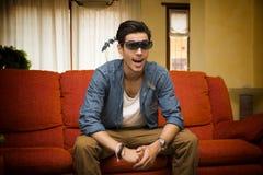 Homem novo que veste os vidros 3d que reagem na surpresa Foto de Stock Royalty Free
