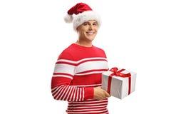 Homem novo que veste um chapéu de Papai Noel e que guarda uma caixa de presente do Natal foto de stock