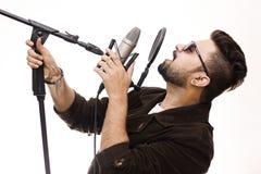 Homem novo que veste um revestimento marrom e os vidros que cantam uma música Imagens de Stock Royalty Free