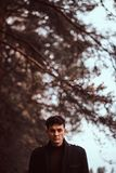 Homem novo que veste um revestimento preto na floresta do outono fotos de stock