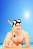 Homem novo que veste uma máscara mergulhando em uma praia Imagem de Stock