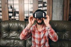 Homem novo que veste vidros da realidade virtual em casa imagens de stock royalty free
