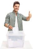 Homem novo que vota e que faz um polegar acima do sinal imagem de stock royalty free