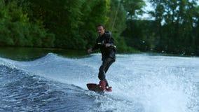 Homem novo que wakeboarding na onda do rio Cavaleiro do embarque da vigília video estoque