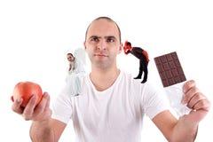 Homem novo rasgado entre comer uma maçã e um choco foto de stock royalty free