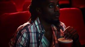 Homem novo redigido que olha um filme vídeos de arquivo