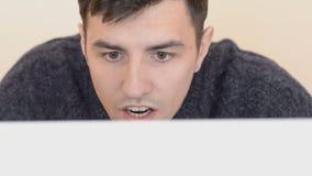 Homem novo redigido que trabalha no computador vídeos de arquivo