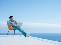 Homem novo relaxado em casa no balcão imagem de stock royalty free