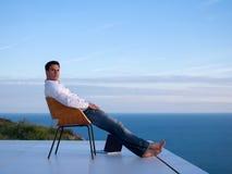 Homem novo relaxado em casa no balcão imagem de stock