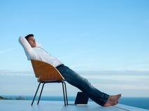 Homem novo relaxado em casa no balcão imagens de stock royalty free