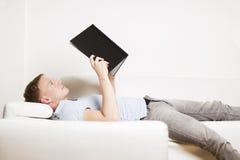 Homem novo relaxado que lê um livro e que encontra-se no sofá. imagens de stock