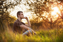 Homem novo relaxado que senta-se na grama Fotos de Stock Royalty Free