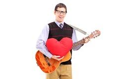 Homem novo romântico que joga uma guitarra acústica e que guardara um vermelho Fotografia de Stock