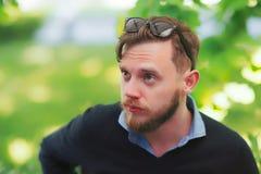 Homem novo sério com os óculos de sol no café da rua fotos de stock royalty free