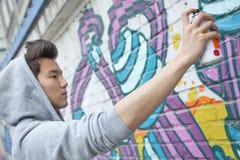 Homem novo sério que concentra-se ao guardar uma lata de pulverizador e uma pintura de pulverizador em uma parede fora Foto de Stock