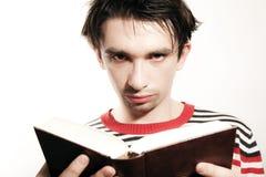 Homem novo sério que lê um livro Fotos de Stock Royalty Free