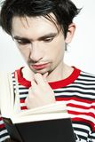 Homem novo sério que lê um livro Imagem de Stock Royalty Free