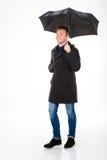 Homem novo satisfeito feliz no revestimento que anda sob o guarda-chuva fotos de stock